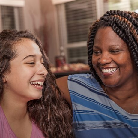 Multi-ethnic family.  Latin and African descent teenage girls and their mom in home setting.  Single mom and group looks at camera as they talk together in living room.  Girl at left is adopted or a foster child.  Mixed race, blended families.
